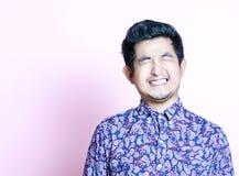 Junger Geeky asiatischer Mann im bunten Hemd, das beide Augen schließt Lizenzfreies Stockbild