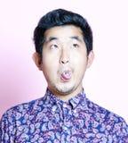 Junger Geeky asiatischer Mann im bunten Hemd, das lustiges Gesicht zieht Stockfotos