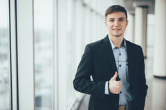 Junger gehender Daumen des Geschäftsmannes oben im Büro Lizenzfreie Stockfotografie