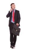 Junger gehender Geschäftsmann beim Halten eines Aktenkoffers Lizenzfreies Stockbild