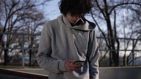 Junger gelockter vorangegangener m?nnlicher Skateboardfahrer, der in seinem Handy im Rochenpark an einem sonnigen Tag grast Lehne