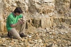 Junger Geologe, der Felsentypen studiert stockbilder