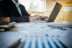 Junger Geschäftsführer, der im Büro mit Laptop und financi arbeitet Lizenzfreies Stockbild
