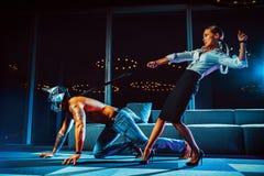 Junger Geschäftsfrau-Holdingmann auf Leine lizenzfreies stockfoto