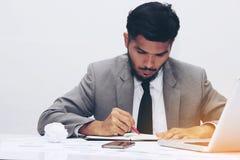 Junger Geschäftsmann arbeitet an Schreibtisch Stockfotografie