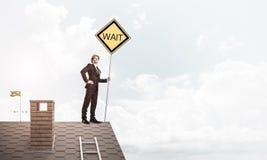 Junger Geschäftsmann auf dem Hausziegelsteindach, das gelbes Schild hält Lizenzfreie Stockfotografie