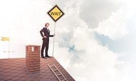 Junger Geschäftsmann auf dem Hausziegelsteindach, das gelbes Schild hält Lizenzfreies Stockfoto