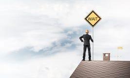 Junger Geschäftsmann auf dem Hausziegelsteindach, das gelbes Schild hält Lizenzfreies Stockbild