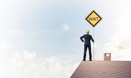 Junger Geschäftsmann auf dem Hausziegelsteindach, das gelbes Schild hält Stockbild