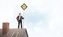 Junger Geschäftsmann auf dem Hausziegelsteindach, das gelbes Schild hält Lizenzfreie Stockfotos