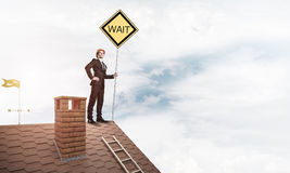 Junger Geschäftsmann auf dem Hausziegelsteindach, das gelbes Schild hält Stockfotos