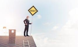 Junger Geschäftsmann auf dem Hausziegelsteindach, das gelbes Schild hält Lizenzfreie Stockbilder