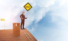 Junger Geschäftsmann auf dem Hausziegelsteindach, das gelbes Schild hält Gemischte Medien Lizenzfreies Stockbild