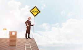 Junger Geschäftsmann auf dem Hausziegelsteindach, das gelbes Schild hält Gemischte Medien Lizenzfreie Stockfotografie