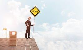 Junger Geschäftsmann auf dem Hausziegelsteindach, das gelbes Schild hält Gemischte Medien Lizenzfreie Stockbilder