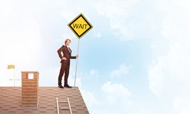 Junger Geschäftsmann auf dem Hausziegelsteindach, das gelbes Schild hält Gemischte Medien Stockfotos