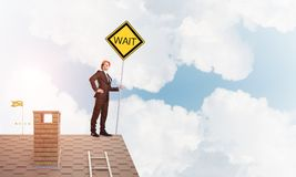 Junger Geschäftsmann auf dem Hausziegelsteindach, das gelbes Schild hält Gemischte Medien Stockfotografie