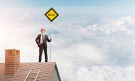 Junger Geschäftsmann auf dem Hausziegelsteindach, das gelbes Schild hält Gemischte Medien Lizenzfreie Stockfotos