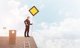 Junger Geschäftsmann auf dem Hausziegelsteindach, das gelbes Schild hält Gemischte Medien Stockfoto