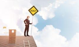 Junger Geschäftsmann auf dem Hausziegelsteindach, das gelbes Schild hält Gemischte Medien Stockbilder