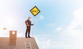 Junger Geschäftsmann auf dem Hausziegelsteindach, das gelbes Schild hält Gemischte Medien Lizenzfreies Stockfoto