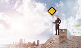 Junger Geschäftsmann auf dem Hausziegelsteindach, das gelbes Schild hält und Stadt betrachtet Gemischte Medien Lizenzfreies Stockbild