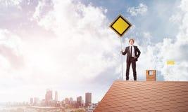 Junger Geschäftsmann auf dem Hausziegelsteindach, das gelbes Schild hält und Stadt betrachtet Gemischte Medien Stockbild