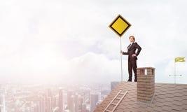 Junger Geschäftsmann auf dem Hausziegelsteindach, das gelbes Schild hält und Stadt betrachtet Gemischte Medien Stockfotografie