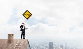 Junger Geschäftsmann auf dem Hausziegelsteindach, das gelbes Schild hält und Stadt betrachtet Gemischte Medien Lizenzfreie Stockfotografie