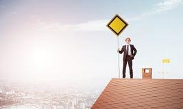 Junger Geschäftsmann auf dem Hausziegelsteindach, das gelbes Schild hält und Stadt betrachtet Gemischte Medien Lizenzfreies Stockfoto