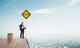 Junger Geschäftsmann auf dem Hausziegelsteindach, das gelbes Schild hält und Stadt betrachtet Gemischte Medien Stockbilder