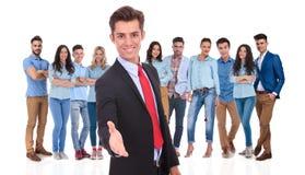 Junger Geschäftsmann begrüßt Sie zu seinem Team mit einem Händedruck Lizenzfreies Stockbild