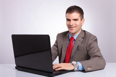 Junger Geschäftsmann betrachtet Sie beim Arbeiten an Laptop stockbilder