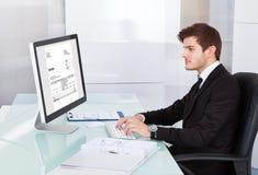 Junger Geschäftsmann, der auf Computer am Schreibtisch verwendet Stockfotografie