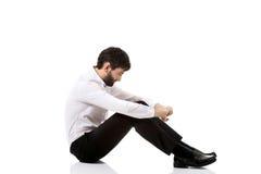 Junger Geschäftsmann, der auf dem Boden sitzt Stockfotos