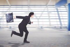 Junger Geschäftsmann, der auf dem Flughafenabfertigungsgebäude läuft lizenzfreies stockbild