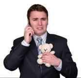 Junger Geschäftsmann, der auf dem Handy, Teddybären kuppelnd schreit. stockbild