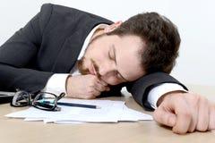Junger Geschäftsmann, der auf dem Schreibtisch schläft stockfotografie