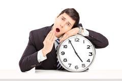 Junger Geschäftsmann, der auf eine große Wanduhr einschläft Lizenzfreie Stockfotos