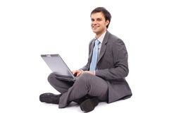 Junger Geschäftsmann, der auf einem Laptop schreibt Lizenzfreie Stockfotos