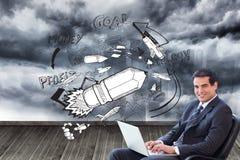 Junger Geschäftsmann, der auf einem Lehnsessel arbeitet mit einem Laptop sitzt Stockbild