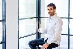 Junger Geschäftsmann, der auf einem Schemel im Büro sitzt Stockfotografie