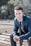Junger Geschäftsmann, der auf einer Bank in der Straße sitzt Stockfotos