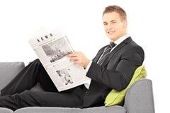 Junger Geschäftsmann, der auf einer Couch mit Zeitung sitzt Stockbild