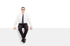 Junger Geschäftsmann, der auf einer leeren Anschlagtafel sitzt Lizenzfreie Stockfotografie