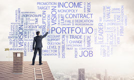 Junger Geschäftsmann, der auf Hausdach steht und Führung schreibt Lizenzfreie Stockfotos