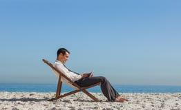 Junger Geschäftsmann, der auf seinem Klappstuhl unter Verwendung seiner Tablette stillsteht lizenzfreies stockfoto