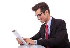 Junger Geschäftsmann, der auf seiner Tabletteauflage durchstöbert Lizenzfreie Stockfotografie