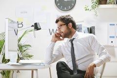 Junger Geschäftsmann, der auf Smartphone im Büro spricht, Lizenzfreies Stockbild
