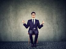 Junger Geschäftsmann, der auf Stuhl meditiert stockfotos